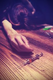 stock photo of addicted  - Vintage toned photo of an unconscious drug addict with syringe young female model poses as drug addict concept photo - JPG