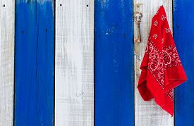picture of skeleton key  - Red handkerchief and bronze skeleton key hanging on blue and white rustic wooden wall - JPG