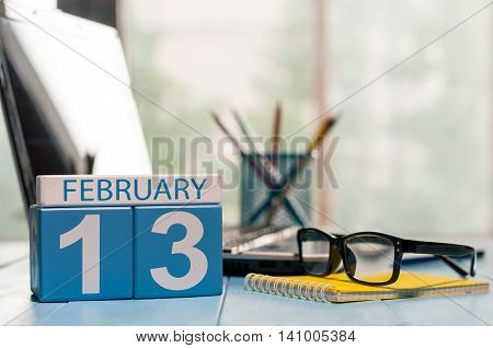 February 13th. Day 13 of month, calendar on designer workplace background. Winter time. Empty space for text.