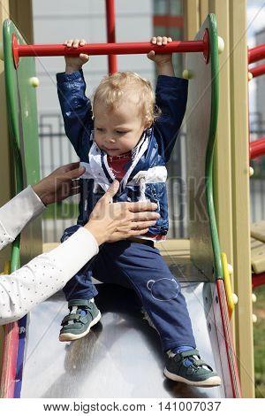 Mother Holding Toddler On Slide