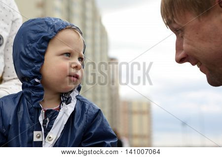 Serious toddler looking at a man outdoor