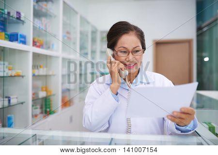 Drugstore worker ordering medication on the phone