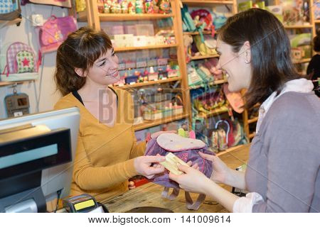female customer making card payment at toy store