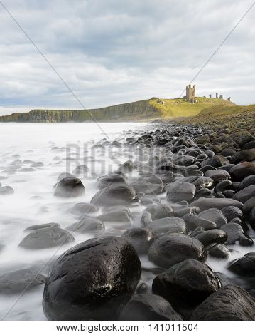 An iconic view of Dunstanburgh Castle from the famous black cobbles, washed by an incoming tide of frothy white waves
