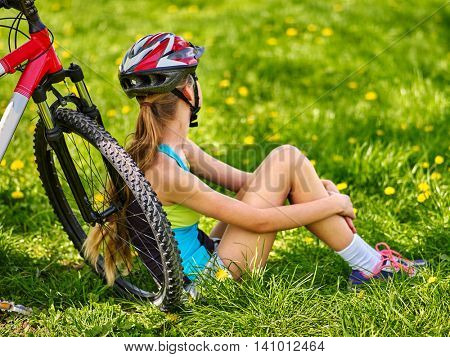 Girl rides bicycle. Bicyclist girl sitting near bicycle. Bicyclist looking into distance.