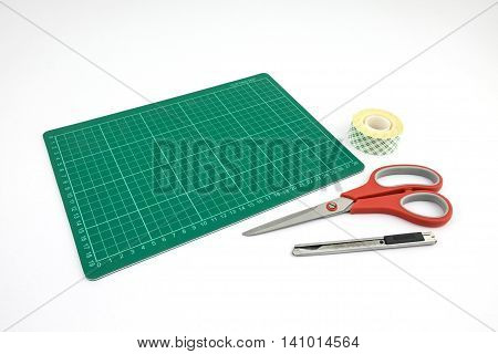 Green cutting mat with cutter Scissors and Tape roll of double-sided adhesive on white background