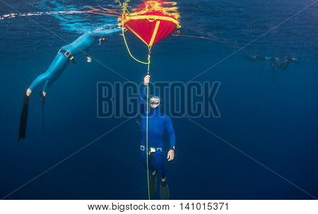 Underwater shot of freediver's couple training in sea with buoy