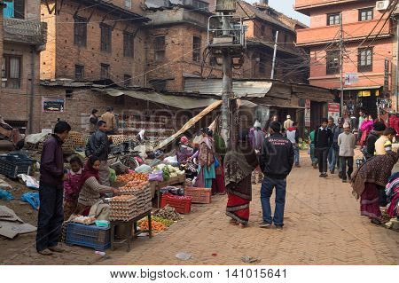 Bhaktapur, Nepal - December 5, 2014: People buying and selling goods at a local market