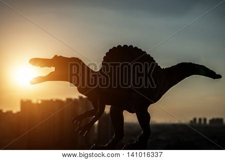 silhouette of spinosaurus and buildings in sunset time