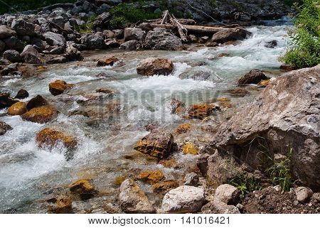 Mountain stream that flowing over yellow rocks