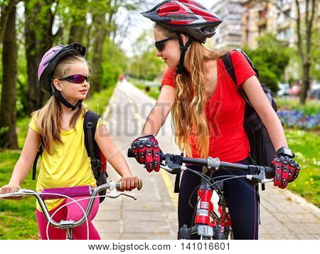 Girls wearing bicycle helmet and glass with rucksack ciclyng bicycle. Girls children cycling on yellow bike lane.