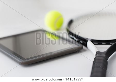 sport, fitness, sports equipment and objects concept - close up of tennis racket with ball and tablet pc computer over white background