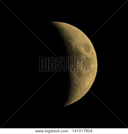 First quarter moon over dark black sky seen with a telescope from northern emisphere at night vintage sepia