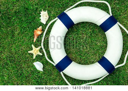 White lifebuoy on green lawn space for text