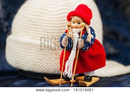 Souvenir little cross country skier on a background of white knitted hat with ear-flaps, for background use.