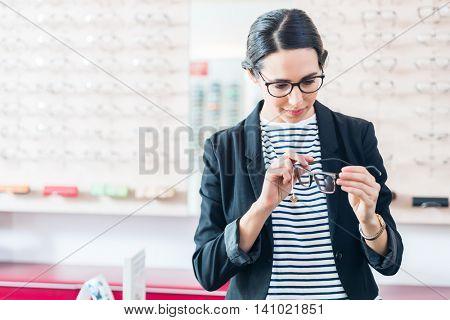 Woman taking glasses off shelf in optician shop