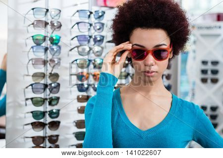 Black woman wearing and buying sunglasses in optician shop