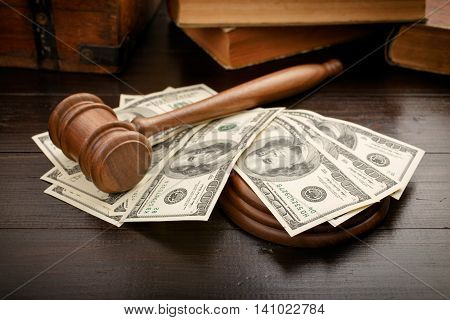 Judge gavel with dollars and law book on brown lacquered wooden desk close up with copy space