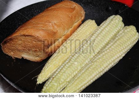 appetizing piece of golden crust  bread and three rolls of young corn