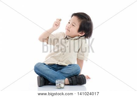 Cute Asian child saving money in glass bottlemoney saving concept