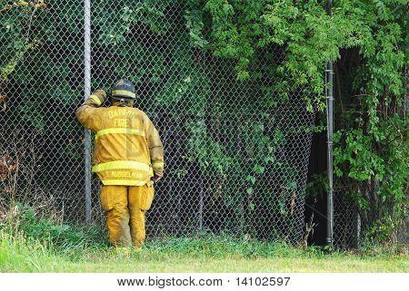 Fireman Peering Through Fence