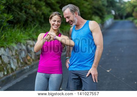 Athletic couple checking time on wristwatch after jogging