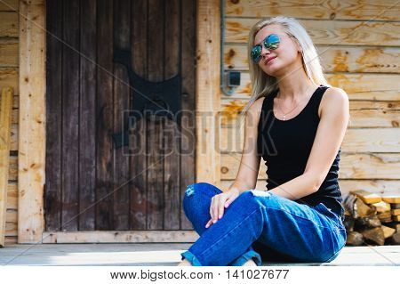 Girl sitting on a porch in a wooden house. Young blonde with sun glasses. Smotrt aside her hands folded in her knees