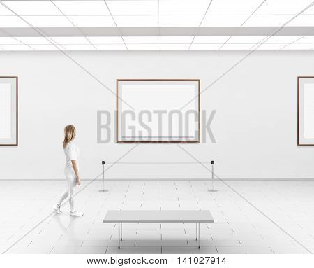Modern gallery wall mockup. Woman walk in museum hall with blank wall with frames. White clear stand mock up show. Display artwork presentation. Art design empty floor. Expo studio wall in center.