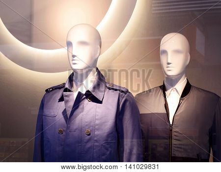 Male plastic mannequins behind a fashion store window. Two white display dummies. View through a shop window.