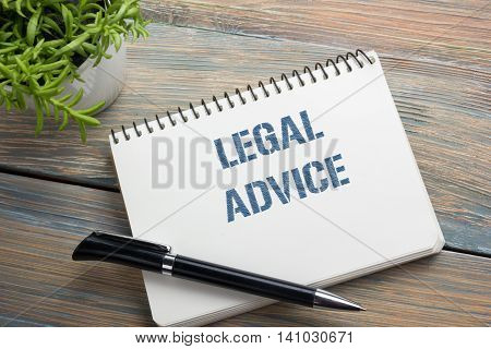 Legal Advice. Notepad with message, pen and flower. Office supplies on desk table top view.