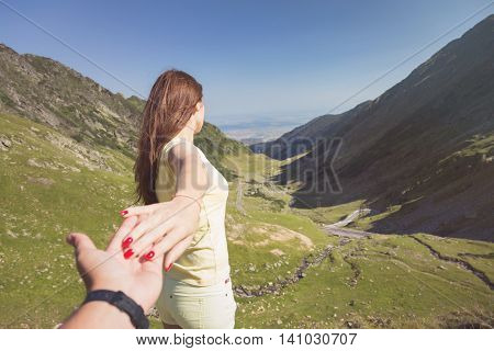 Woman holding man by hand on the top of the mountain. Vintage look