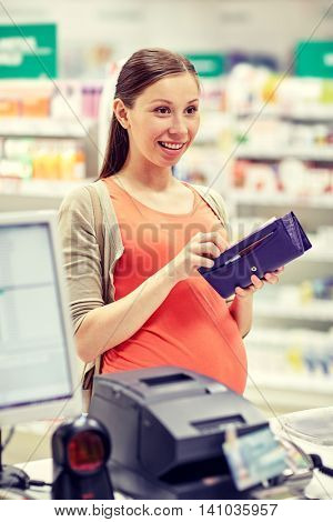 medicine, pharmaceutics, health care and people concept - happy pregnant woman with wallet in at cashbox drugstore