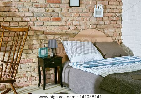 Interior of retro bedroom with bed and brick wall.