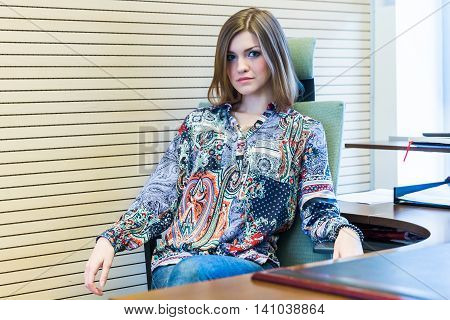 Beautiful Russian girl sits in an office chair of her boss