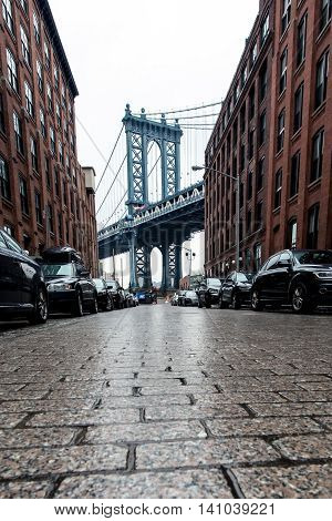Manhattan Bridge framed by brownstone buildings and cobblestone road as seen from Brooklyn