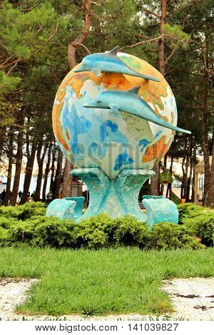 GELENDZHIK, RUSSIA - NOVEMBER 5, 2015: Sculpture World and Dolphins. Two dolphins on background of earth globe. Small architectural form landscape element on November 5, 2015 in city-resort Gelendzhik, Russia