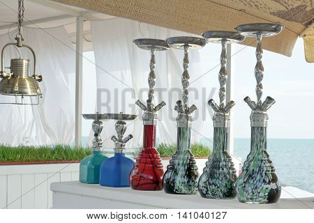 Group Of Modern Ceramic And Glass Hookah Or Shisha Appliance On The White Wooden Bar Counter Sea View Restaurant
