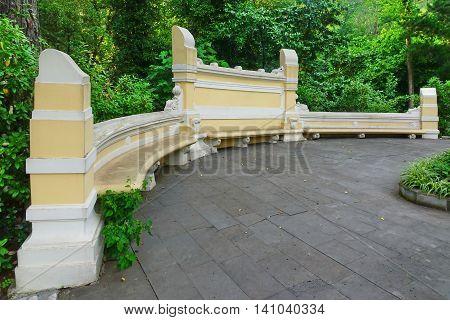 Antique Yellow Stone Bench In The Public Botanical Garden
