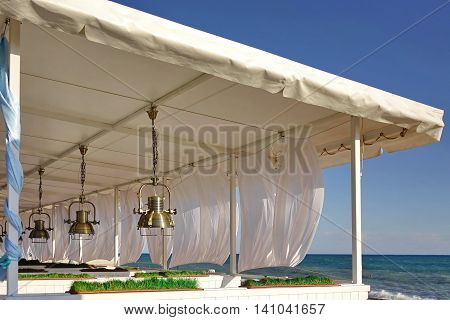 Seaview Restaurant Exterior. White Terrace With Wooden Furniture And Lanterns
