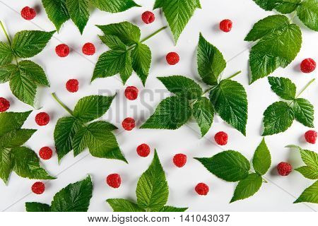 Red fresh raspberries on white background. Scattered natural ripe organic berries with green leaves, top view flat lay