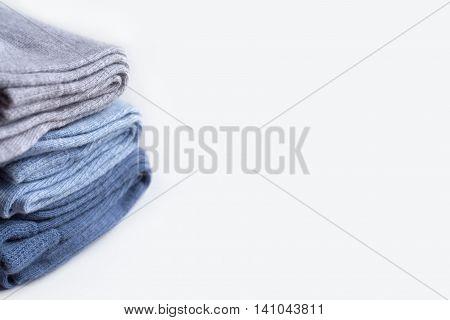 A pile of grey, light cornflower blue, denim knitwear socks isolated on white background.