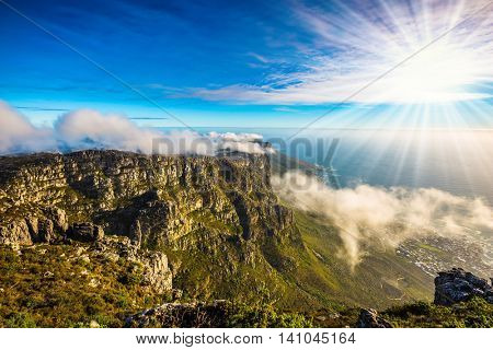 The concept of active tourism and recreation. Travel to Africa. Walk on top of Table Mountain at sunset