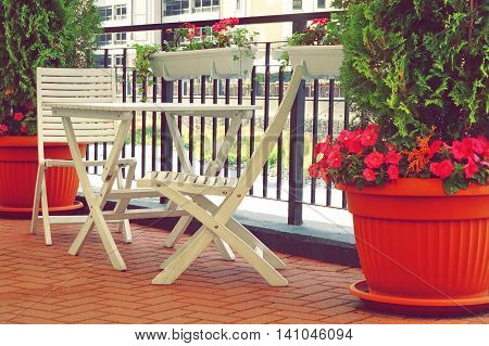 Balcony With Wooden Furniture And Decorative Small Garden.