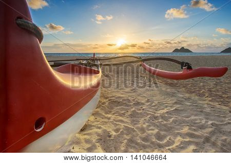 Red and white canoe with outrigger on beach at sunrise