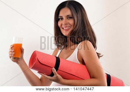 Latin woman holding exercise mat and drinking orange juice bottle after training