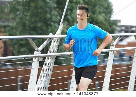 Young Man Running In Urban Setting Listening To Music