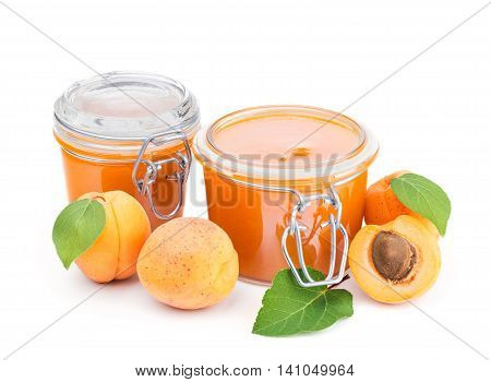 Two jars of apricot jam and fresh fruits isolated on white background