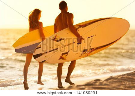 Girl and Boy with Surf Boards at Sunset