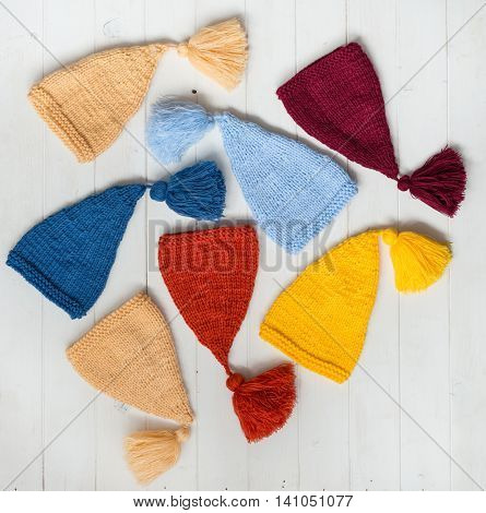 nice colorful hats for babies on white painted table, top view