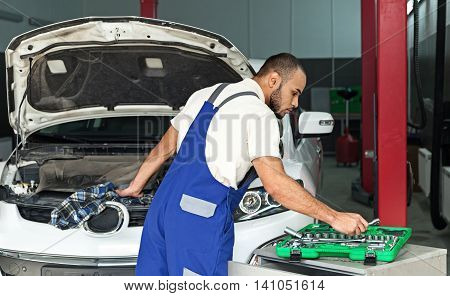 Auto Mechanic Taking a Tool and Working on the Engine of a Car